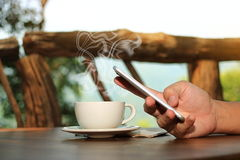 Close up coffee cup with hands of young man holding mobile phone in nature background. Selective focus and shallow depth of field. Stock Images