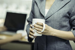Close up of coffee cup holding by a woman Royalty Free Stock Image