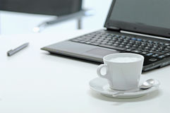 Close up of coffee cup with laptop in background Stock Photography