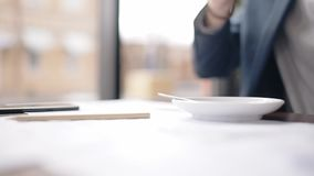Close up of coffee cup taken from the table by businessman hand. stock video footage