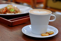 Close up coffee latte art with biscuits on the table. Stock Photo