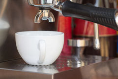 Close up of coffee machine makes coffee and white cup Royalty Free Stock Image