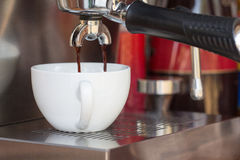 Close up of coffee machine makes coffee and white cup Royalty Free Stock Photo