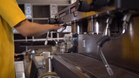 Close up of coffee machine at work. Close up of man in yellow shirt using coffee machine, dolly slide. Shot with Sony a7s and Atomos Ninja Flame stock video footage
