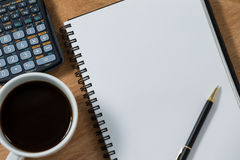 Close-up of coffee mug with blank diary, pen and calculator. On wooden table Stock Photo