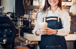Close up on coffee take away cup with asian woman owner barista Royalty Free Stock Photography