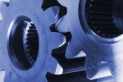 Close-up of cogs in blue. Two gear-wheels in bluish, detailed Stock Images