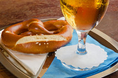 Close-up of cold beer in a glass with pretzel. A close-up of a glass of cold beer and a pretzel served on a metal tray with white and blue serviettes on an old Royalty Free Stock Image