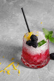 Close-up of a cold berry drink. Beverage with mint, lemon peel and blackberries on a gray stone background. Stock Photography
