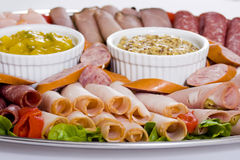Close Up Of Cold Meat Catering Platter. With salami, cabana sausage and seeded wholegrain mustard and sweet mustard pickle. Lettuce and roasted red capsicum royalty free stock photo