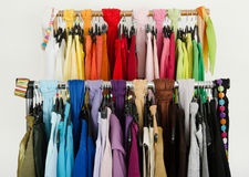Close up on color coordinated clothes on hangers in a store. Royalty Free Stock Image
