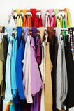 Close up on color coordinated clothes on hangers in a store. Royalty Free Stock Photos