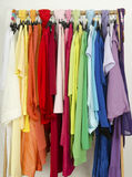 Close up on color coordinated clothes on hangers in a store. Stock Images