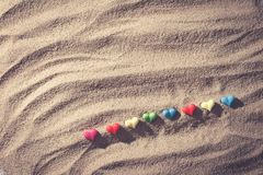 Sand beach. Close up color of mini heart on sand of beach from top view, with vintage tone effect Royalty Free Stock Photo