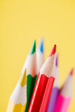 Close up of color pencils with different color over yellow background Stock Photos