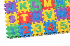 Close up of colored alphabet puzzle. Multi colored alphabet puzzle on white background Royalty Free Stock Images