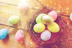 Close up of colored easter eggs in nest on wood Royalty Free Stock Images