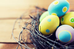 Close up of colored easter eggs in nest on wood Stock Photos