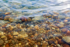 Close up of colored stones under salty water at the Dead Sea coa. St, Jordan Stock Photography