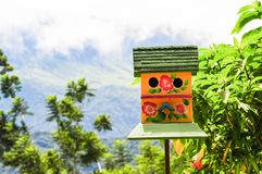 Close up of a colorful bird house in a garden royalty free stock photo
