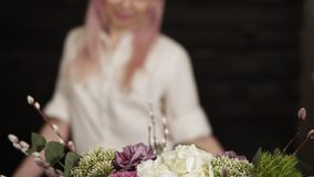 Close-up of a colorful bouquet on the table changing to a footage of an attractive young smiling girl. Dark background. Slow motion stock footage