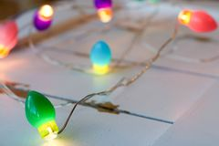 Colorful lights on white wood. Close up of colorful and bright Christmas lights on a rustic white wood background Royalty Free Stock Photo