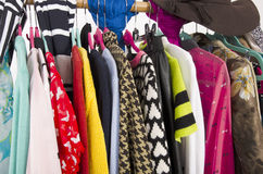 Close up on colorful clothes and hat on hangers in a store. Stock Photo