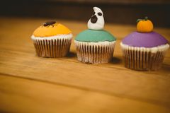 Colorful cup cakes on table during Halloween. Close up of colorful cup cakes on wooden table during Halloween Stock Image