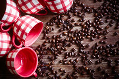 Close-up of colorful cups and coffee beans on wooden table Stock Image