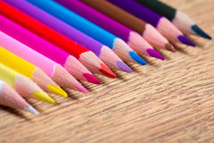 Close up of colorful drawing pencils row on wooden table Royalty Free Stock Photos