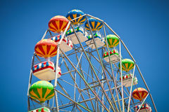 Close-up of colorful ferris wheel on vivid blue sky Stock Images