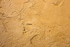 Close-up of colorful golden bronze plastered uneven stucco wall. Abstract texture, chaotic copy space background. Decorative. Grunge space royalty free stock image