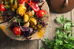 Close Up of Colorful Grilled Vegetable Bounty Tray on Wooden Pan. And Dip Resting on Painted Picnic Table stock image