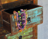 Close up colorful jewellery in old painted wooden drawer royalty free stock photos
