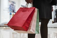Close up of colorful paper bags in woman's hands on shopping centre background. Woman in skirt and black tights standing in mall royalty free stock images