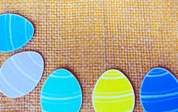 Close-up of colorful paper eggs silhouette frames against canvas background.  Royalty Free Stock Photo