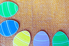 Close-up of colorful paper eggs silhouette frames against canvas background.  Royalty Free Stock Photos
