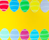 Close-up of colorful paper eggs silhouette frames against golden background.  Stock Image