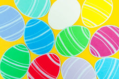 Close-up of colorful paper eggs silhouette frames against golden background.  Royalty Free Stock Image