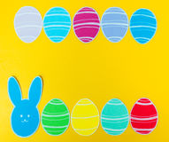 Close-up of colorful paper rabbit and paper eggs silhouette frames against canvas background.  Royalty Free Stock Photography