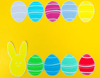 Close-up of colorful paper rabbit and paper eggs silhouette frames against canvas background.  Stock Photo
