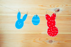 Close-up of colorful paper rabbits and paper egg silhouette frames hanging on a cord against wooden background.  Royalty Free Stock Photography