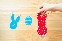 Close-up of colorful paper rabbits and paper egg silhouette frames hanging on a cord against wooden background. Hand hanging a pap. Er rabbit Stock Photo
