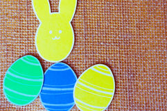 Close-up of colorful paper rabbits and paper eggs silhouette frames against canvas background.  Stock Photography