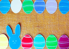 Close-up of colorful paper rabbits and paper eggs silhouette frames against canvas background.  Stock Photos