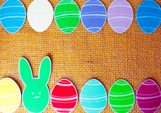 Close-up of colorful paper rabbits and paper eggs silhouette frames against canvas background.  Stock Image