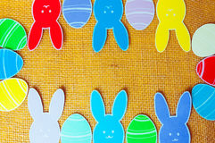 Close-up of colorful paper rabbits and paper eggs silhouette frames against canvas background.  Royalty Free Stock Images