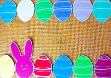 Close-up of colorful paper rabbits and paper eggs silhouette frames against canvas background.  Stock Images