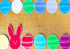Close-up of colorful paper rabbits and paper eggs silhouette frames against canvas background.  Royalty Free Stock Image