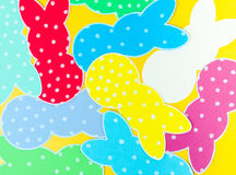 Close-up of colorful paper rabbits silhouette frames against golden background.  Royalty Free Stock Photo